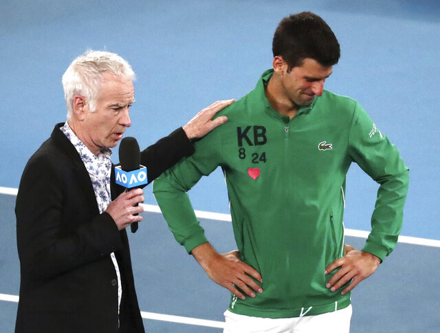 Serbia's Novak Djokovic reacts as he is interviewed by John McEnroe about the death of his friend Kobe Bryant following his quarterfinal win over Canada's Milos Raonic at the Australian Open tennis championship in Melbourne, Australia, Tuesday, Jan. 28, 2020.(AP Photo/Dita Alangkara)