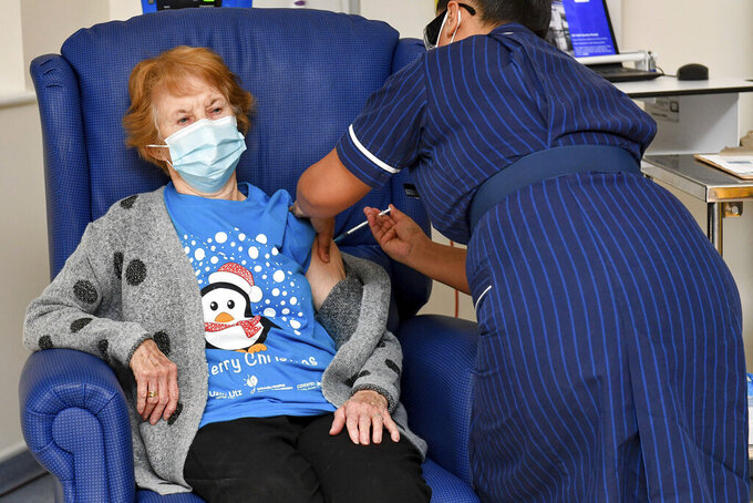 """FILE - In this Tuesday Dec. 8, 2020 file photo, 90-year-old Margaret Keenan, the first patient in the U.K. to receive the Pfizer-BioNTech COVID-19 vaccine, receives an injection by nurse May Parsons at University Hospital, Coventry, England. On Friday, Dec. 11, 2020, The Associated Press reported on stories circulating online incorrectly asserting the first two recipients of the COVID-19 vaccine in Britain are """"crisis actors."""" Parsons first administered the vaccine to Keenan, then to """"Bill"""" William Shakespeare. (Jacob King/Pool via AP)"""