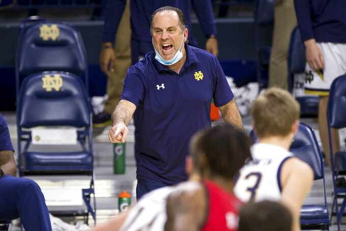 FILE - In this March 3, 2021, file photo, Notre Dame head coach Mike Brey directs players during the first half of an NCAA college basketball game against North Carolina State in South Bend, Ind. Coming off an 11-15 campaign which ended with a 101-59 loss to North Carolina in the ACC Tournament — his most lopsided loss ever in 21 previous seasons as Notre Dame's winningest men's coach — Brey adds an impressive grad transfer in former Yale standout Paul Atkinson and two hometown freshmen to a senior-laden lineup led by Prentiss Hubb, Nate Laszewski and Dane Goodwin and hopes that will be enough to return the Fighting Irish to the NCAA Tournament for the first time since the 2016-17 season. (AP Photo/Robert Franklin, File)