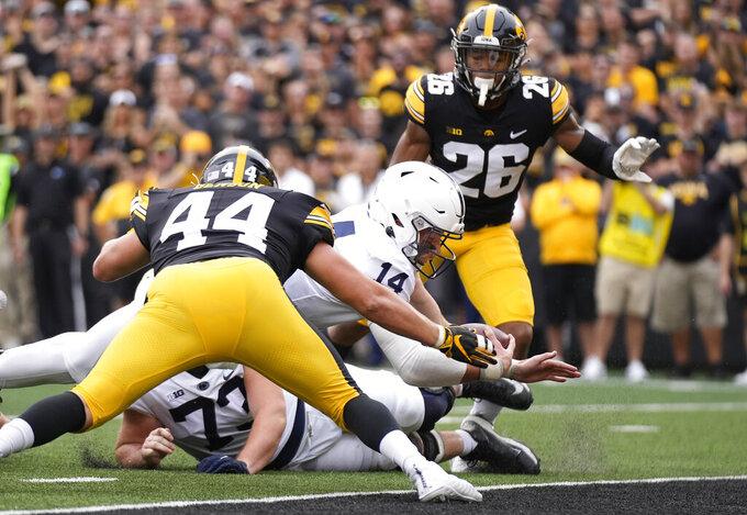 Penn State quarterback Sean Clifford (14) dives in for a touchdown past Iowa linebacker Seth Benson (44) during the first half of an NCAA college football game, Saturday, Oct. 9, 2021, in Iowa City, Iowa. (AP Photo/Matthew Putney)