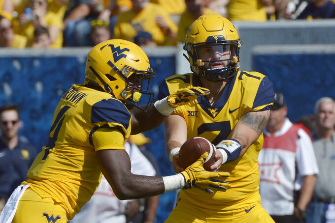 West Virginia quarterback Will Grier (7) hands off the football to running back Leddie Brown (4) during the first half of an NCAA college football game against Kansas in Morgantown, W. Va., Saturday Oct. 6, 2018. (AP Photo/Craig Hudson)
