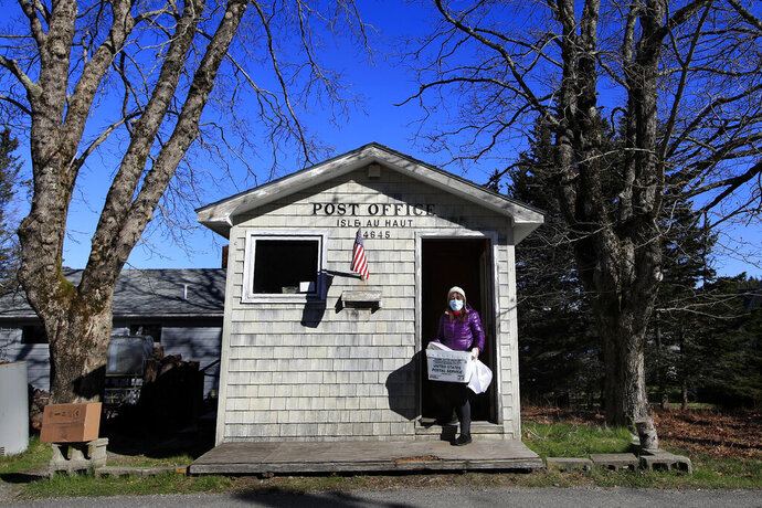 In this Wednesday, May 6, 2020, photo, Postmistress Donna DeWitt carries mail at the tiny post office on Isle Au Haut, Maine. The post office serves the 70 or so year-round island residents. (AP Photo/Robert F. Bukaty)