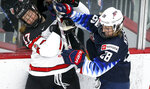 Canada's Ella Shelton, left, is checked by United States' Amanda Kessel during the third period of an IIHF women's world hockey championships game Thursday, Aug. 26, 2021, in Calgary, Alberta. (Jeff McIntosh/The Canadian Press via AP)