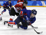 South Korea's Lee Jingyu (29), of the combined Koreas team, falls as she passes the puck against Haruna Yoneyama (10), of Japan, during the first period of the preliminary round of the women's hockey game at the 2018 Winter Olympics in Gangneung, South Korea, Wednesday, Feb. 14, 2018. (AP Photo/Matt Slocum)