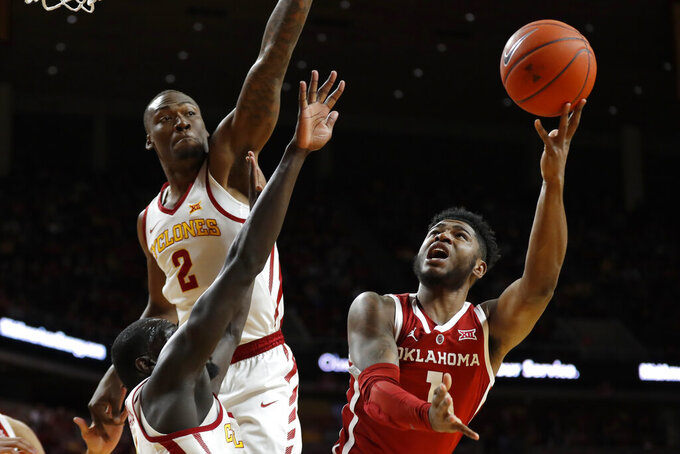 Oklahoma guard Rashard Odomes, right, shoots over Iowa State's Marial Shayok and Cameron Lard (2) during the first half of an NCAA college basketball game, Monday, Feb. 25, 2019, in Ames, Iowa. (AP Photo/Charlie Neibergall)