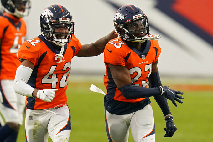 Denver Broncos cornerback Parnell Motley, left, celebrates after cornerback Michael Ojemudia (23) forced a fumble against the Las Vegas Raiders during the first half of an NFL football game, Sunday, Jan. 3, 2021, in Denver. (AP Photo/Jack Dempsey)
