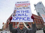 Cathy Clark holds a sign and yells during a protest in downtown Fort Worth, Texas, Monday, Feb. 18, 2019. People gathered on the Presidents Day holiday to protest President Donald Trump's recent national emergency declaration. (AP Photo/LM Otero)