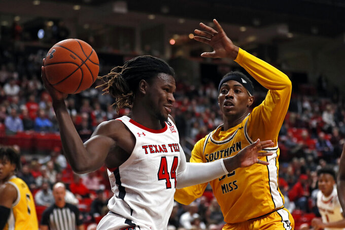 Texas Tech's Chris Clarke (44) passes the ball around Southern Mississippi's Leonard Harper-Baker (32) during the first half of an NCAA college basketball game Monday, Dec. 16, 2019, in Lubbock, Texas. (Brad Tollefson/Lubbock Avalanche-Journal via AP)