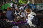 A group of farmers share a hookah as they chat while blocking a major highway in protest against new farm laws at the Delhi-Uttar Pradesh state border, India, Monday, Jan. 11, 2021. (AP Photo/Altaf Qadri)