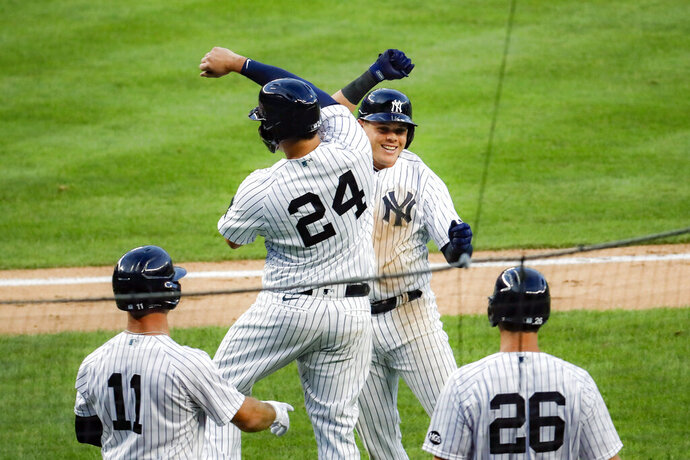 New York Yankees' Gio Urshela, top right, celebrates with teammate Gary Sanchez (24) after hitting a grand slam off Boston Red Sox starting pitcher Zack Godley in the second inning of a baseball game Saturday, Aug. 1, 2020, in New York. (AP Photo/John Minchillo)