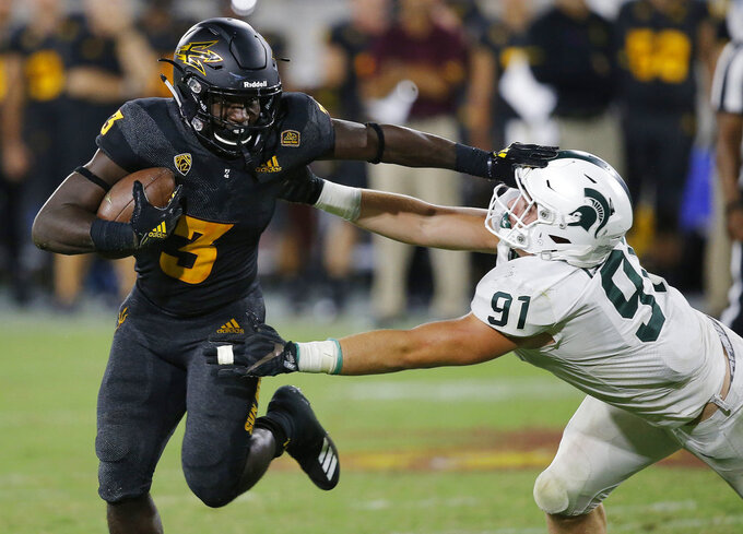 FILE - In this Sept. 8, 2018, file photo, Arizona State running back Eno Benjamin (3) gives Michigan State defensive end Jack Camper (91) a stiff arm as he tries to get past during the second half of an NCAA college football game, in Tempe, Ariz. Benjamin set the school's single-game rushing record last week when he rumbled for 312 yards in the Sun Devils' 52-24 win over Oregon State. Colorado (4-0, 1-0) hosts Arizona State (3-2, 1-0) on Saturday. (AP Photo/Ross D. Franklin, File)