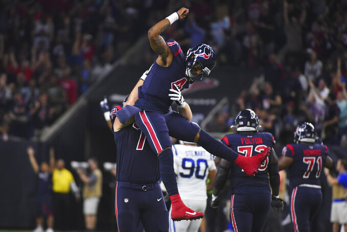 Houston Texans quarterback Deshaun Watson (4) celebrates with teammates after conceding on a pass with wide receiver DeAndre Hopkins (10) for a touchdown against the Indianapolis Colts during the first half of an NFL football game Thursday, Nov. 21, 2019, in Houston. (AP Photo/Eric Christian Smith)
