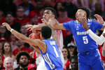 Houston forward Fabian White Jr., middle, attempts to control a rebound as Memphis guard Tyler Harris (1) and guard Boogie Ellis (5) reach in during the first half of an NCAA college basketball game Sunday, March 8, 2020, in Houston. (AP Photo/Michael Wyke)