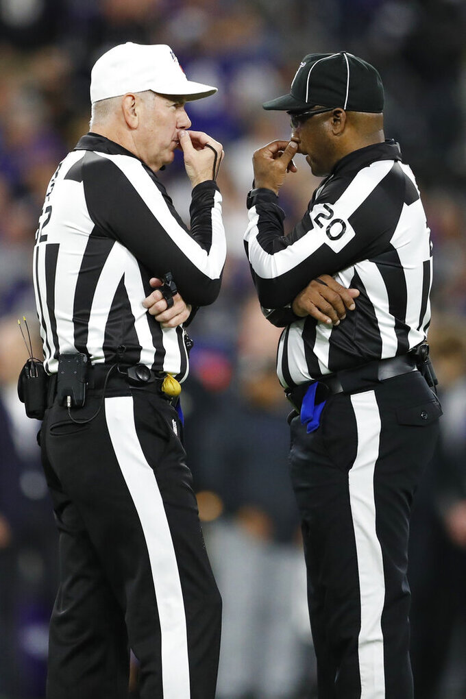 Umpire Barry Anderson (20) confers with referee Bill Vinovich during the first half an NFL divisional playoff football game between the Baltimore Ravens and the Tennessee Titans, Saturday, Jan. 11, 2020, in Baltimore. (AP Photo/Julio Cortez)