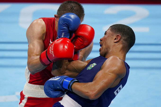 Ukraine's Oleksandr Khyzhniak, left exchanges punches with Brazil's Hebert Sousa during their men's middleweight 75-kg boxing gold medal match at the 2020 Summer Olympics, Saturday, Aug. 7, 2021, in Tokyo, Japan. (AP Photo/Frank Franklin II)