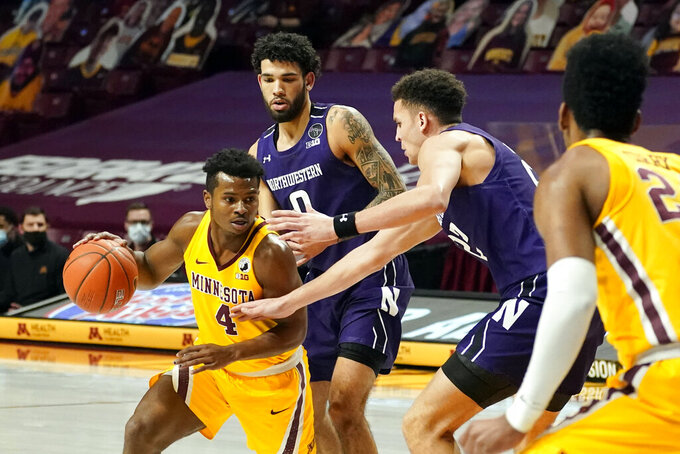 Minnesota's Jamal Mashburn Jr. (4) shrives as Northwestern's Pete Nance, second from right, defends in the first half of an NCAA college basketball game, Thursday, Feb. 25, 2021, in Minneapolis. (AP Photo/Jim Mone)
