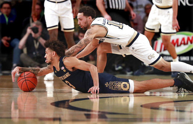 Notre Dame guard Prentiss Hubb, left, and Georgia Tech guard Jose Alvarado dive for the ball during the first half of an NCAA college basketball game Wednesday, Jan. 15, 2020, in Atlanta. (Curtis Compton/Atlanta Journal-Constitution via AP)