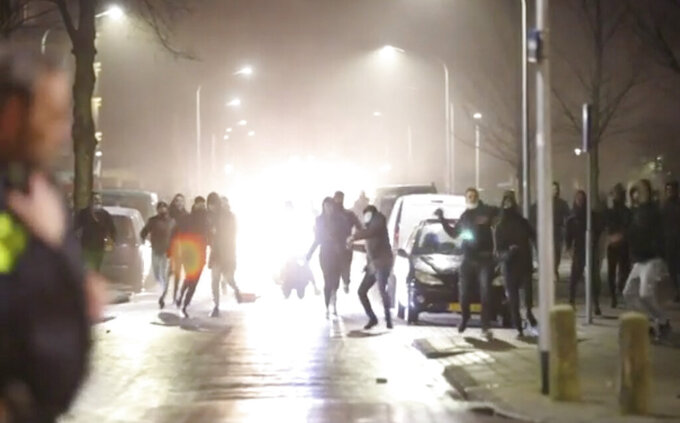 In this grab taken from video on Monday, Jan, 25, 2021, rioters throw stones at police, in Haarlem, Netherlands. Groups of youths have confronted police in several Dutch cities defying the country's coronavirus curfew and throwing fireworks. Police in the port city of Rotterdam used a water cannon and tear gas in an attempt to disperse a crowd of rioters Monday night. (Mizzle Media via AP)