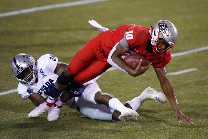 Nevada linebacker Lawson Hall (30) tackles New Mexico quarterback Trae Hall (10) during the second half of an NCAA college football game Saturday, Nov. 14, 2020, in Las Vegas. (AP Photo/John Locher)