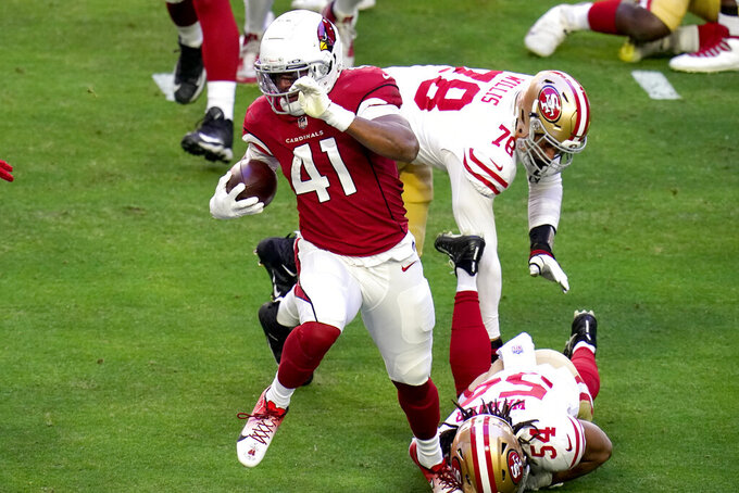 Arizona Cardinals running back Kenyan Drake (41) eludes the tackle of San Francisco 49ers middle linebacker Fred Warner (54) during the first half of an NFL football game, Saturday, Dec. 26, 2020, in Glendale, Ariz. (AP Photo/Ross D. Franklin)