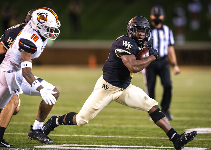 Wake Forest running back Kenneth Walker III carries while pursued by Campbell defensive back James Tarver (16) during an NCAA college football game Friday, Oct. 2, 2020, in Winston-Salem, N.C. (Andrew Dye/The Winston-Salem Journal via AP)