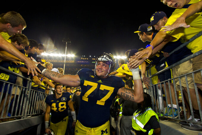 FILE - In this Sept. 7, 2013, file photo, Michigan offensive lineman Taylor Lewan (77) reaches out to young fans as he exits Michigan Stadium, after an NCAA college football game against Notre Dame, in Ann Arbor, Mich. Michigan beat Notre Dame 41-30. (AP Photo/Tony Ding)