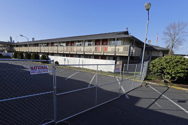 A fence limits access to a back parking area of an Econo Lodge motel in Kent, Wash., Wednesday, March 4, 2020. King County Executive Dow Constantine said Wednesday that the county had purchased the 85-bed motel — which is currently open and operating — south of Seattle to house patients for recovery and isolation due to the COVID-19 coronavirus. (AP Photo/Ted S. Warren)