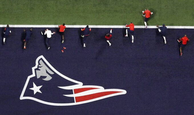 New England Patriots stretch before the NFL Super Bowl 53 football game between the Los Angeles Rams and the New England Patriots Sunday, Feb. 3, 2019, in Atlanta. (AP Photo/Tim Donnelly)