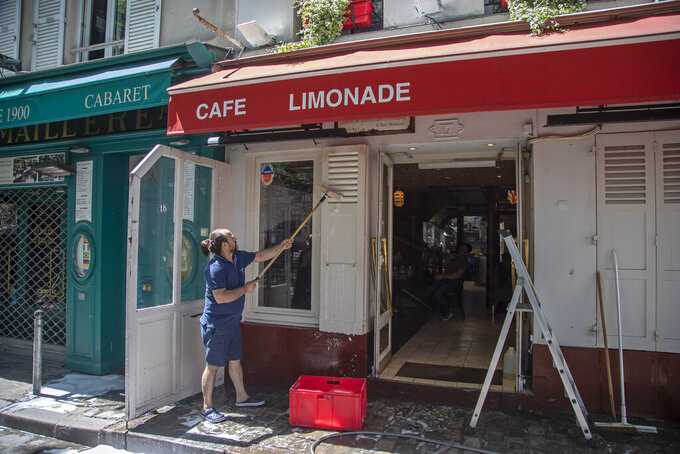 A man cleans the terrace of his restaurant in Paris, Friday, May 29, 2020, as France gradually lifts its Covid-19 lockdown. France is reopening next week its restaurants, bars and cafes starting next week as the country eases most restrictions amid the coronavirus crisis. (AP Photo/Michel Euler)