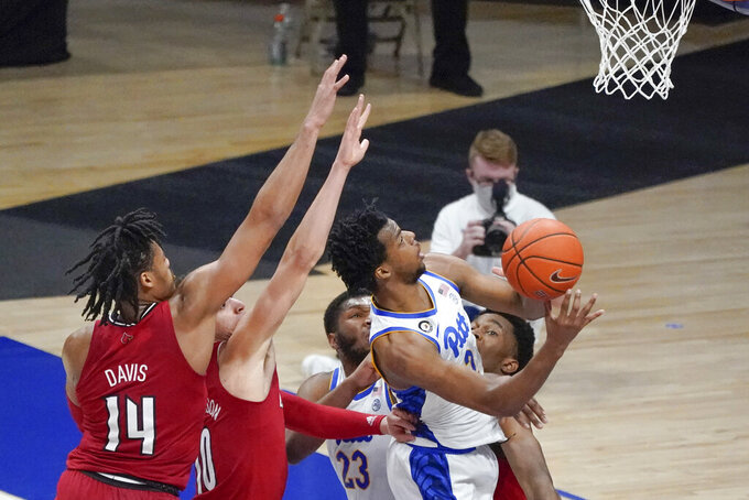 Pittsburgh's Femi Odukale (2) shoots after getting by Louisville's Dre Davis (14) and Samuell Williamson (10) during the second half of an NCAA college basketball game Tuesday, Dec. 22, 2020, in Pittsburgh. (AP Photo/Keith Srakocic)
