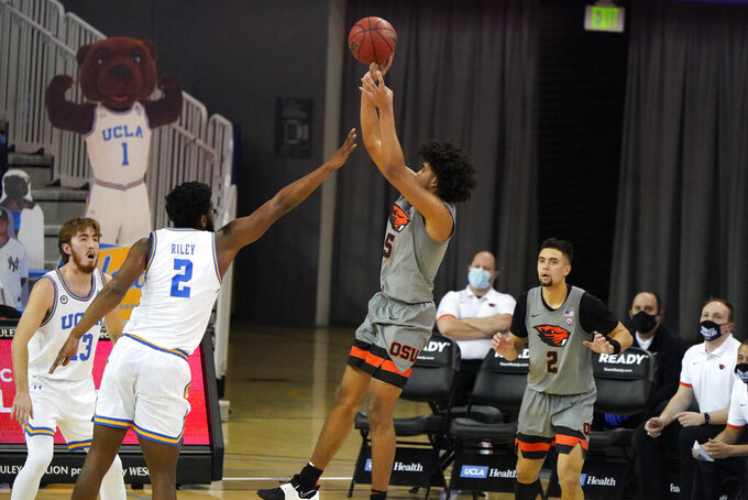 Oregon State guard Ethan Thompson, center, shoots over UCLA forward Cody Riley (2) during the second half of an NCAA college basketball game Saturday, Jan. 30, 2021, in Los Angeles. (AP Photo/Marcio Jose Sanchez)