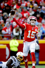 Kansas City Chiefs quarterback Patrick Mahomes (15) throws a pass in front of Los Angeles Chargers defensive end Melvin Ingram III (54) during the first half of an NFL football game in Kansas City, Mo., Sunday, Dec. 29, 2019. (AP Photo/Charlie Riedel)
