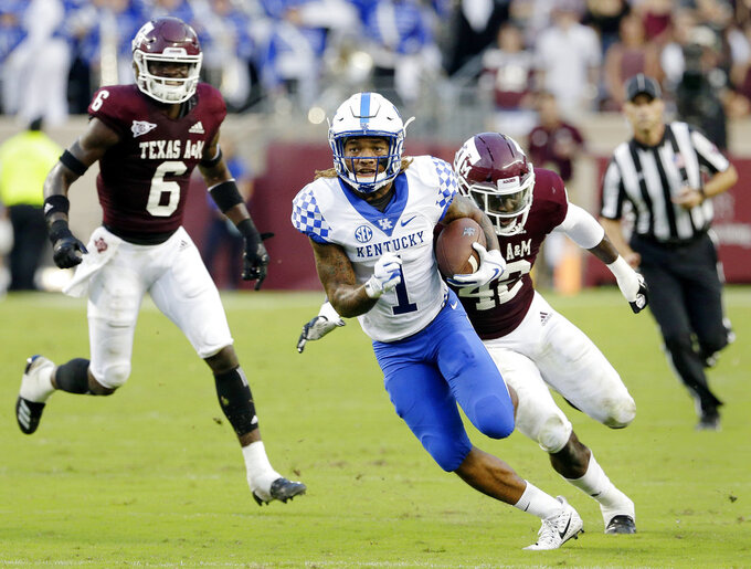 Kentucky wide receiver Lynn Bowden Jr. (1) finds room to score on a run in front of Texas A&M defensive back Donovan Wilson (6) and linebacker Otaro Alaka (42) during the first half of an NCAA college football game Saturday, Oct. 6, 2018, in College Station, Texas. (AP Photo/Michael Wyke)