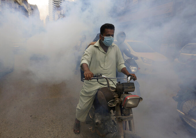 Disinfectant is sprayed in a market area in an effort to contain the outbreak of the coronavirus, in Karachi, Pakistan, Monday, Aug. 2, 2021. (AP Photo/Fareed Khan)