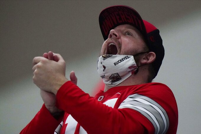 An Ohio State fan cheers before an NCAA College Football Playoff national championship game against Alabama, Monday, Jan. 11, 2021, in Miami Gardens, Fla. (AP Photo/Wilfredo Lee)