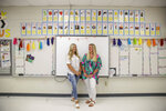 First grade teachers, Ellie Morgan, 25, left, Hannah Sprayberry, 28, right, pose for a portrait, and say they are taking around 5 per-cent pay cut on Thursday, May 28, 2020, in Fort Oglethorpe, Ga. With sharp declines in state spending projected because of the economic fallout from the COVID-19 pandemic, America's more than 13,000 local school systems are wrestling with the likelihood of big budget cuts. (AP Photo/Brynn Anderson)