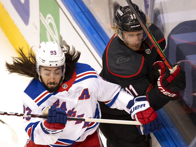 New York Rangers center Mika Zibanejad (93) checks Carolina Hurricanes center Jordan Staal (11) into the boards during the first period of an NHL Stanley Cup playoff hockey game in Toronto, Monday, Aug. 3, 2020. (Frank Gunn/The Canadian Press via AP)