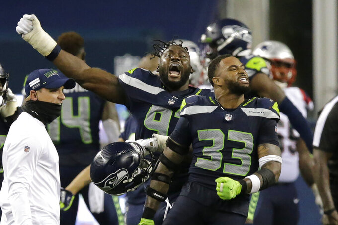 Seattle Seahawks' Jamal Adams (33) and L.J. Collier, left, celebrate after the Seahawks beat the New England Patriots 35-30 in an NFL football game, Sunday, Sept. 20, 2020, in Seattle. (AP Photo/John Froschauer)