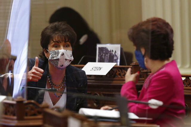 State Sen. Connie Leyva, D-Chino, left, gives a thumbs up as she talks with Sen. Anna Caballero, D-Salinas, at the Capitol, in Sacramento, Calif., Thursday, June 25, 2020. The Senate is expected to vote on Thursday, on a state budget plan that has the backing of both Gov. Gavin Newsom and Democratic Legislative leaders. (AP Photo/Rich Pedroncelli)