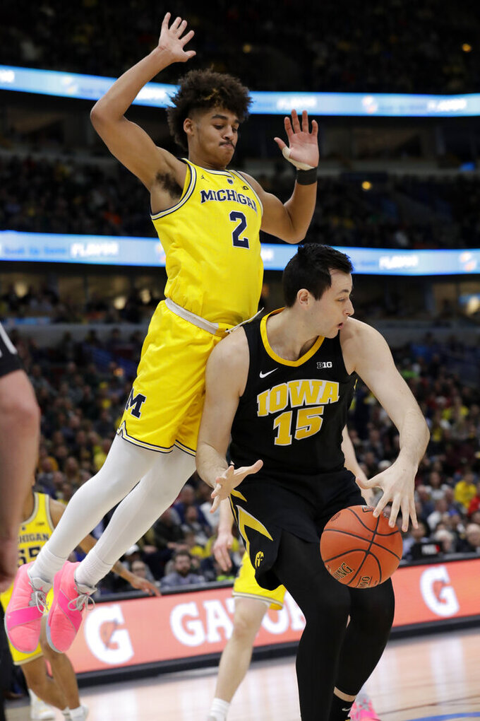 Michigan's Jordan Poole (2) collides with Iowa's Ryan Kriener (15) during the first half of an NCAA college basketball game in the quarterfinals of the Big Ten Conference tournament, Friday, March 15, 2019, in Chicago. (AP Photo/Nam Y. Huh)