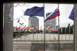 Slovenian and EU flags are seen through a window of the parliament building, in Ljubljana, Thursday, Sept. 16, 2021, broken by anti-COVID measures protesters the previous night. Slovenia has introduced a mandatory anti-COVID vaccination for all civil service employees, further tightening anti-coronavirus measures that have triggered a major riot in the small Alpine state. The measure passed Friday Sept. 17, 2021 says that all state administration employees will need to be vaccinated with one shot by Oct. 1 and by Nov. 1 with the second, unless it's the one-dose Johnson & Johnson vaccine. (AP Photo)