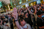 Pro-democracy activists flash three-fingered salute while listening to the national anthem outside Siam Paragon, one of the largest shopping malls, in Bangkok, Thailand, Tuesday, Oct. 20, 2020. Thailand's Cabinet on Tuesday approved a request to recall Parliament for a special session to deal with the political pressures from ongoing anti-government protests. The Cabinet at its weekly meeting approved the request, which calls for a non-voting session on Oct. 26-27. (AP Photo/Sakchai Lalit)