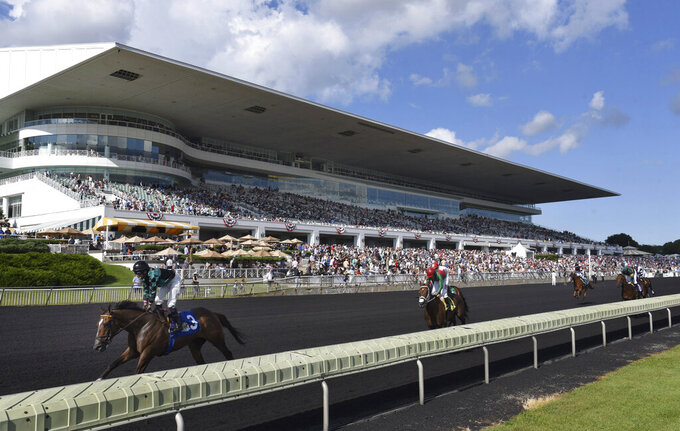 FILE - In this Aug. 12, 2017, file photo, horses in the Bruce D. Memorial Stakes pass the grandstand at Arlington International Racecourse in Arlington Heights, Ill. The Chicago Bears have submitted a bid to buy a spacious suburban horse racing track site. Their announcement signals a potential willingness to move out of downtown Soldier Field for a new stadium. Bears President and CEO Ted Phillips says the club wants to purchase the Arlington International Racecourse. ( John Starks/Daily Herald via AP)
