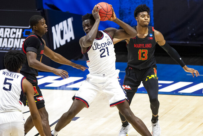 Connecticut's Adama Sanogo (21) holds the ball between Maryland's Darryl Morsell, left, and Hakim Hart (13) during the first half of a first-round game in the NCAA men's college basketball tournament Saturday, March 20, 2021, at Mackey Arena in West Lafayette, Ind. (AP Photo/Robert Franklin)