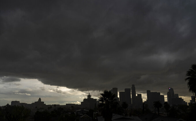 """FILE - In this Jan. 23, 2021, file photo, heavy clouds move over Los Angeles city skyline. California's hopes for a wet """"March miracle"""" did not materialize and a dousing of April 2021 showers may as well be a mirage at this point. California Gov. Gavin Newsom on Monday, May 10, 2021, declared a drought emergency for most of California, extending a previous order that affected two counties to 41 counties throughout much of the state. (AP Photo/Damian Dovarganes, File)"""