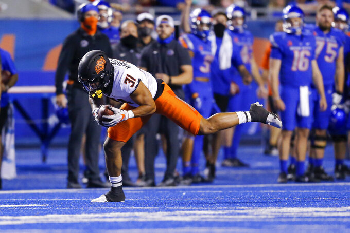 Oklahoma State safety Kolby Harvell-Peel makes an interception against Boise State during the second half of an NCAA college football game Saturday, Sept. 18, 2021, in Boise, Idaho. (AP Photo/Steve Conner)