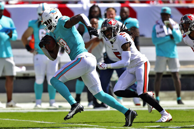 Miami Dolphins wide receiver Preston Williams (18) outruns Tampa Bay Buccaneers cornerback Richard Sherman (5) after a reception during the first half of an NFL football game Sunday, Oct. 10, 2021, in Tampa, Fla. (AP Photo/Mark LoMoglio)