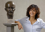 French microbiologist Emmanuelle Charpentier poses near a statue of Max Planck in Berlin, Germany, Wednesday, Oct. 7, 2020. French scientist Emmanuelle Charpentier and American Jennifer A. Doudna have won the Nobel Prize 2020 in chemistry for developing a method of genome editing likened to 'molecular scissors' that offer the promise of one day curing genetic diseases. (AP Photo/Markus Schreiber)