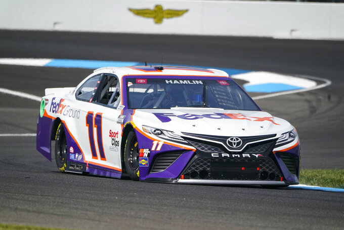 Denny Hamlin (11) drives through a turn during practice for the NASCAR Cup Series auto race at Indianapolis Motor Speedway in Indianapolis, Saturday, Aug. 14, 2021. (AP Photo/Michael Conroy)