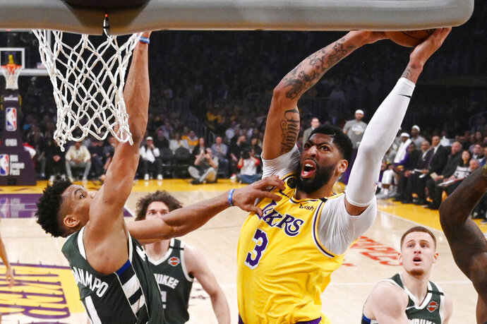 FILE - In this March 6, 2020, file photo, Los Angeles Lakers forward Anthony Davis, right, shoots as Milwaukee Bucks forward Giannis Antetokounmpo defends during the first half of an NBA basketball game in Los Angeles. Davis and the Lakers were leading the Western Conference when the coronavirus pandemic caused the suspension of the NBA season, but he is confident they'll be able to resume their title chase. (AP Photo/Mark J. Terrill, File)